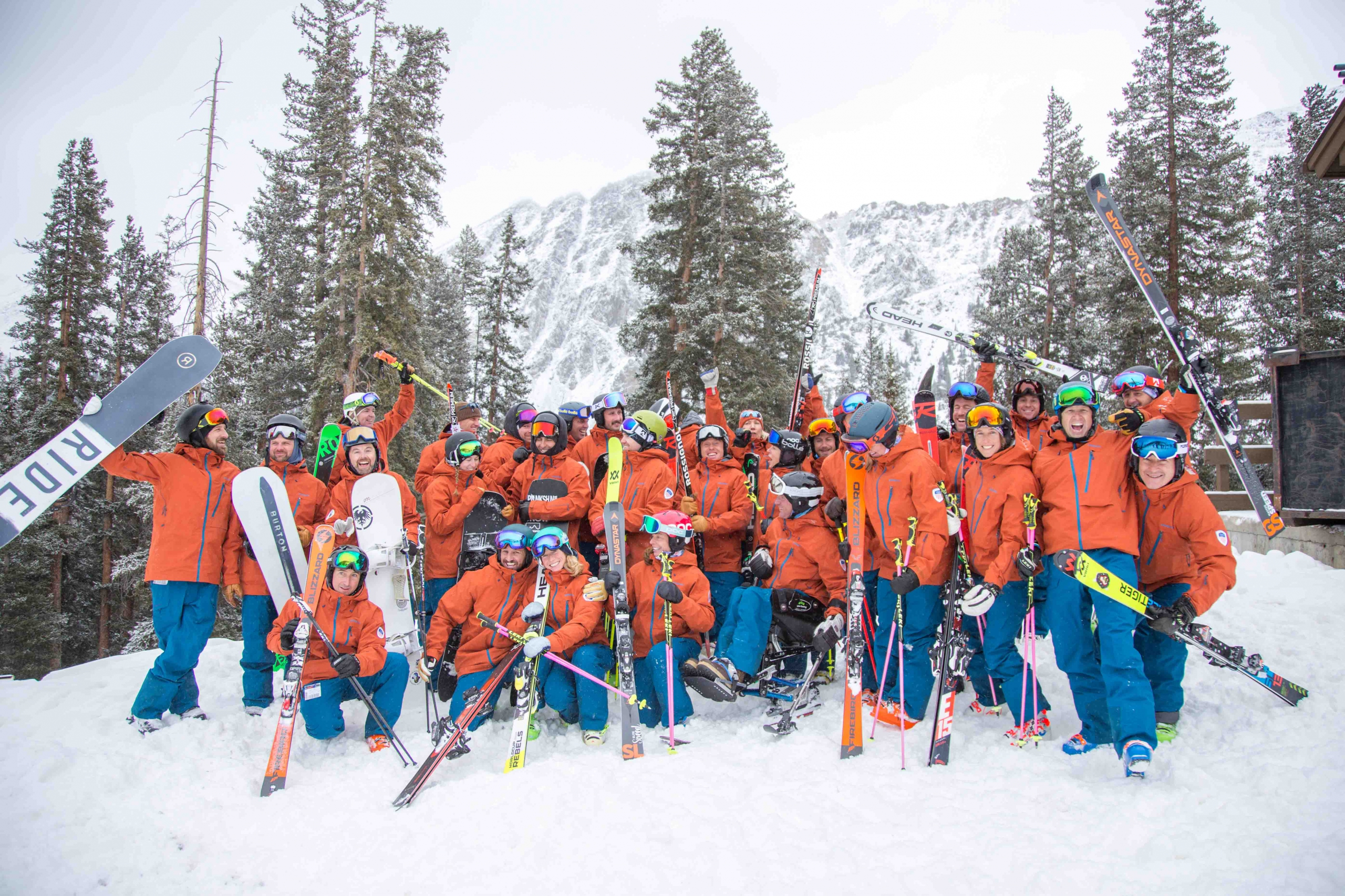 PSIA-AASI National Team celebrates outside in front of snow covered trees holding their skis and snowboards in the air
