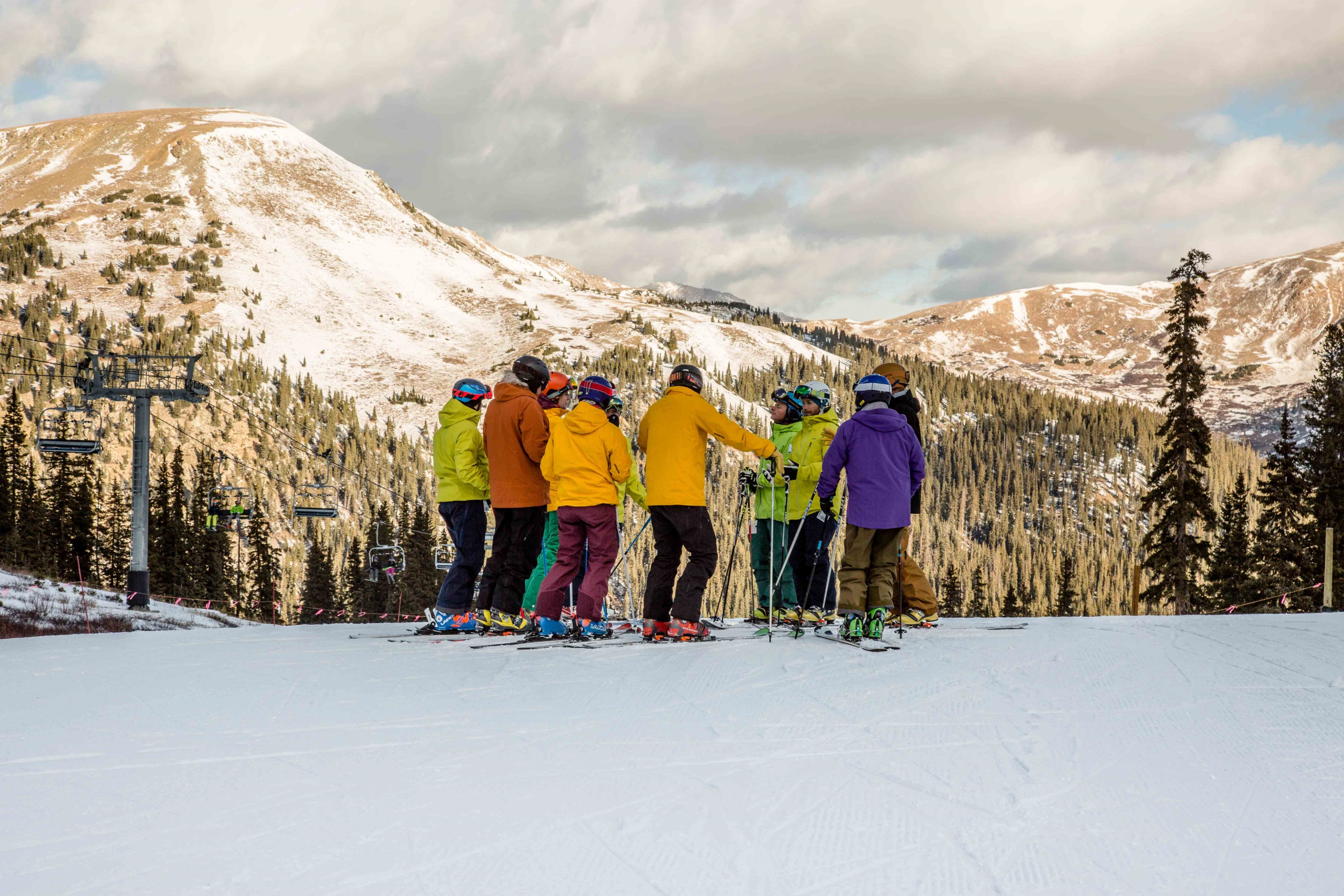 A group of alpine and telemark skiers gathers in a circle at the top of a run during the afternoon alpenglow