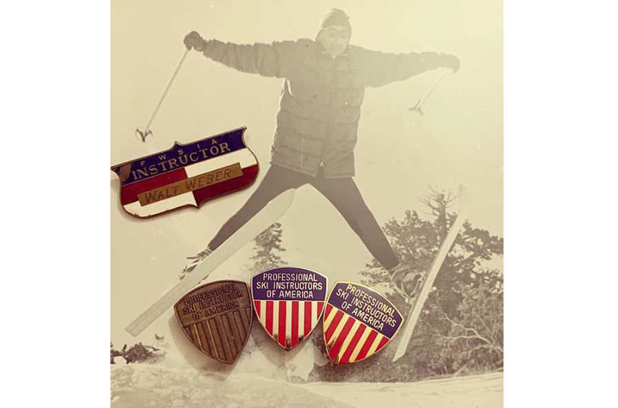A collection of PSIA-AASI pins and Walt Weber's vintage name badge sitting on a historic ski photo of him.