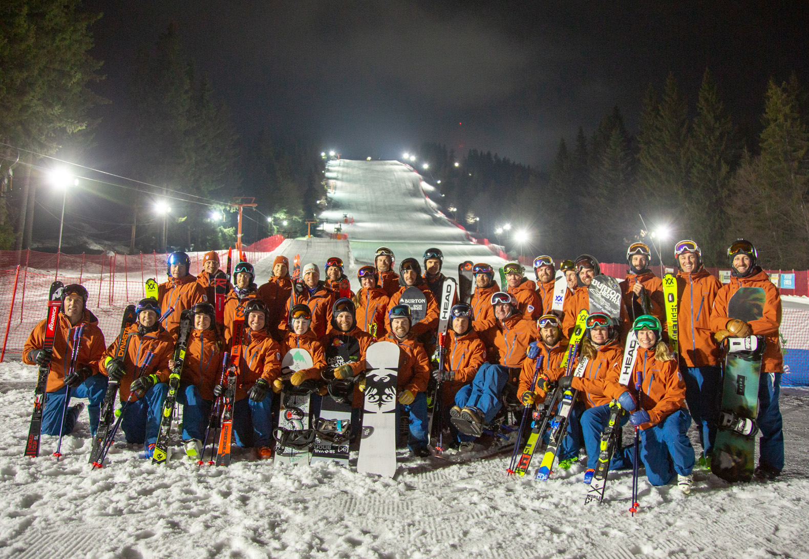 The PSIA-AASI National Team together at the base at the night skiing demo hill at Interski 2019