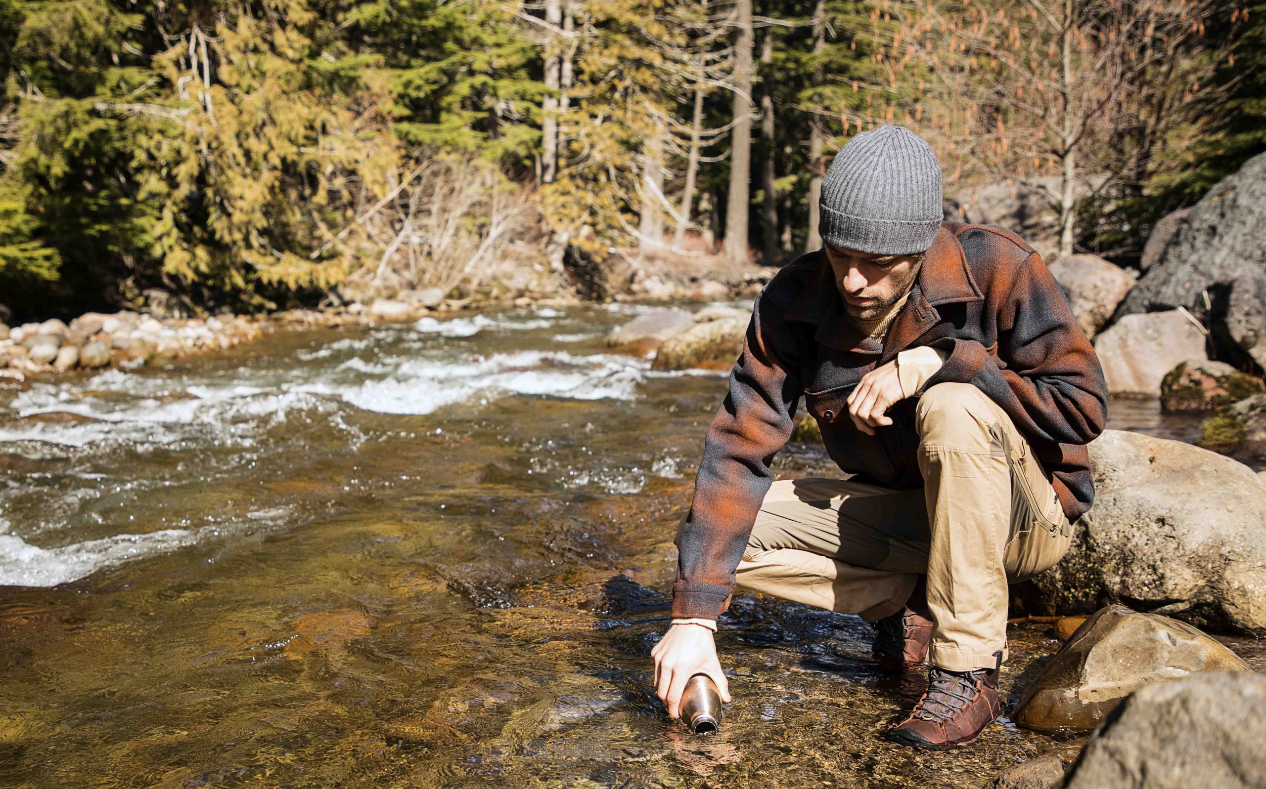 A man in a flannel and beanie stands by a stream in his KEEN boots and fills a water bottle
