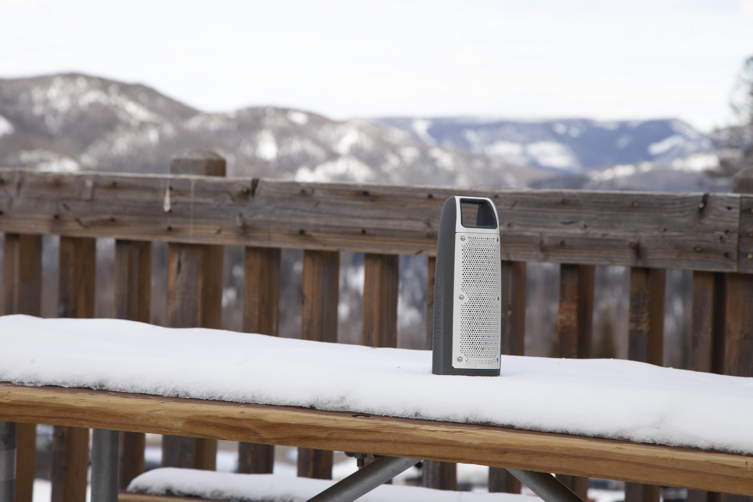 A Kicker Bullfrog speaker sits on a snowy picnic table on an outside deck