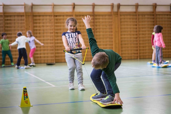 One student pulls another on a Burton Riglet board in their gym class
