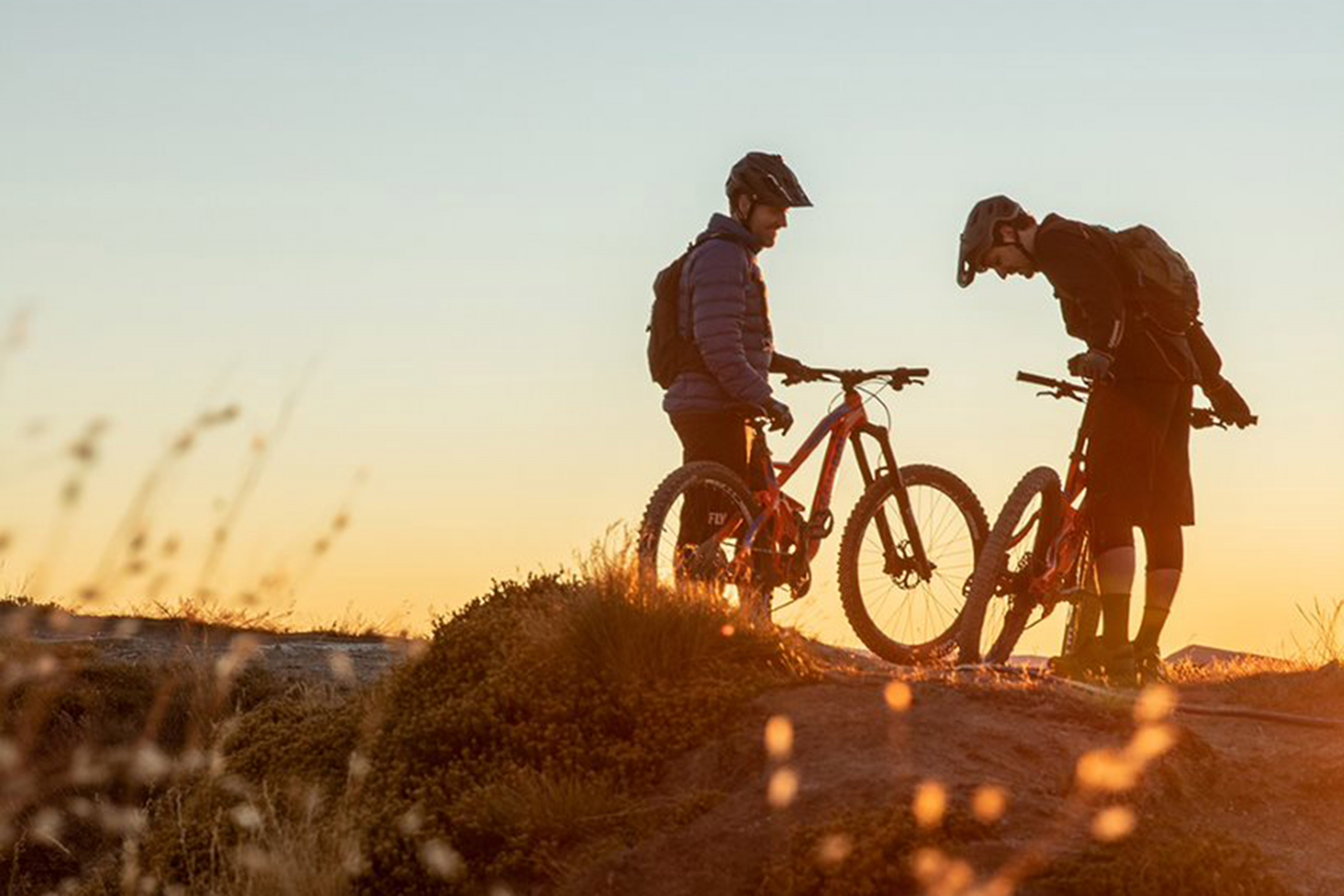 Two mountain bikers on Rossignol bikes at dusk.