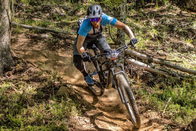 A professional mountain bikers rides a downhill course.