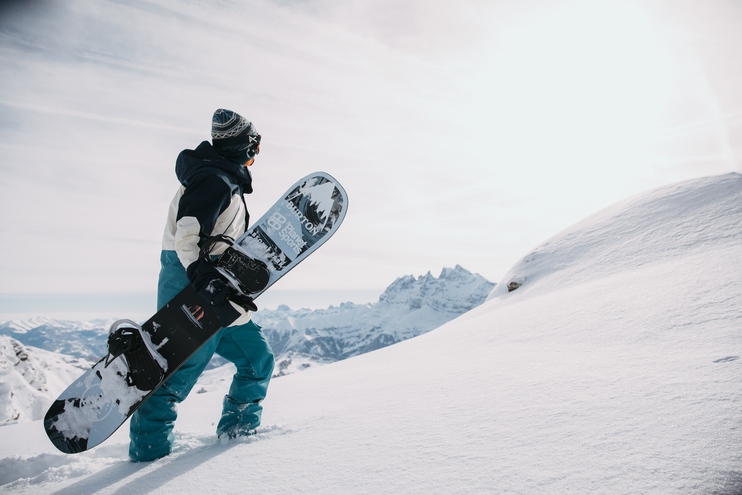 A snowboarder holds their board and walks up a slope