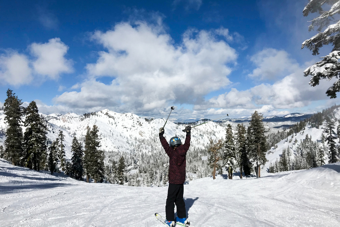 A person skis with their poles above their head in celebration.