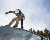 A snowboarder rides over a rainbow rail
